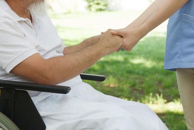 手を取り合う老人と介護員