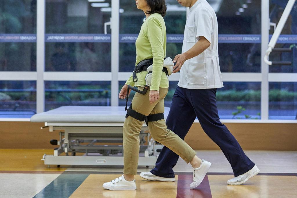 ロボットリハビリテーションを受ける女性と理学療法士
